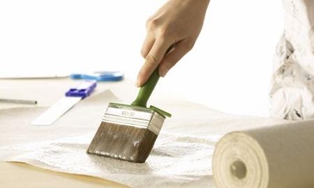 Woman pastes wallpaper